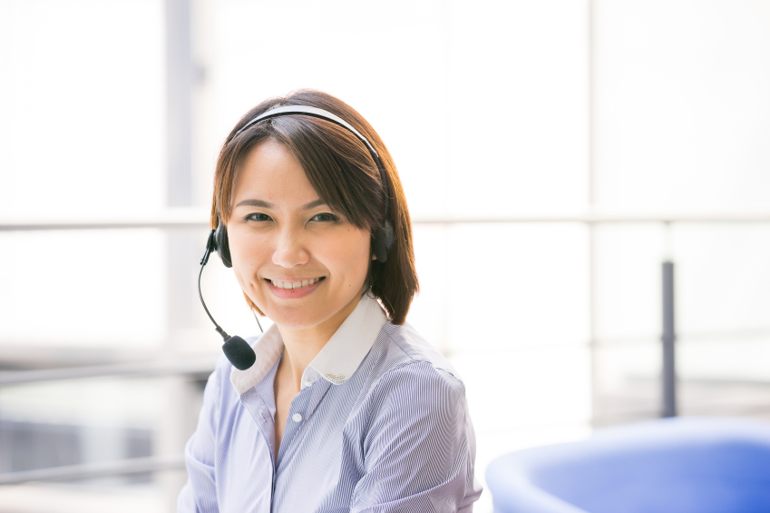 Asian Business woman talking using her headset in the office
