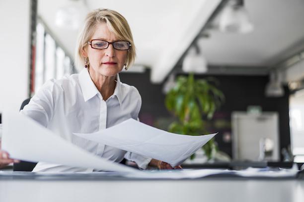 Businesswoman examining documents at desk